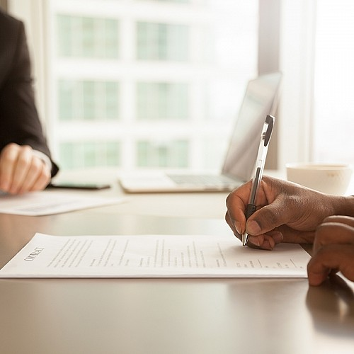 Photograph of two people at a conference table. African American male is signing a contract or agreement